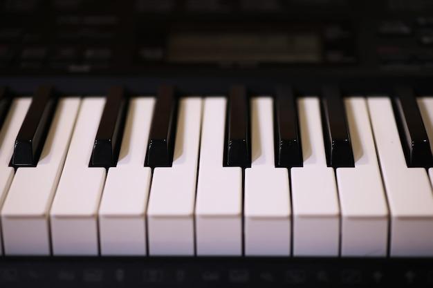 Teclas de piano antiguas. vista cercana de efecto de color blanco y posterior, concepto de fondo de instrumentos musicales