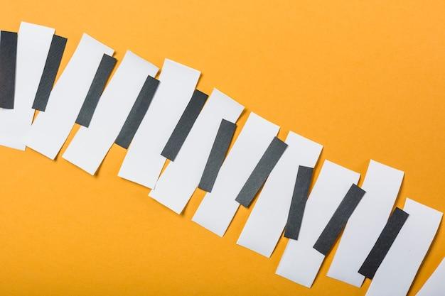Teclas de piano hechas con papel blanco y negro sobre fondo amarillo.