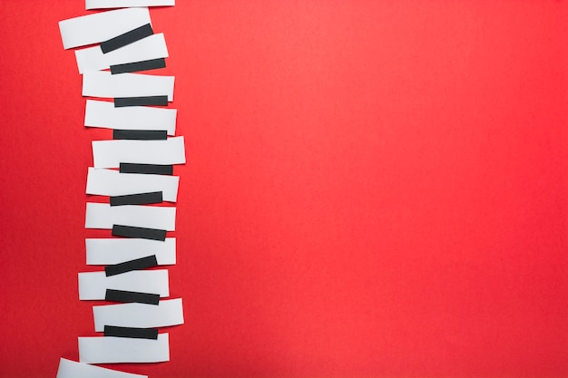Teclas de piano hechas con papel blanco y negro sobre fondo rojo.