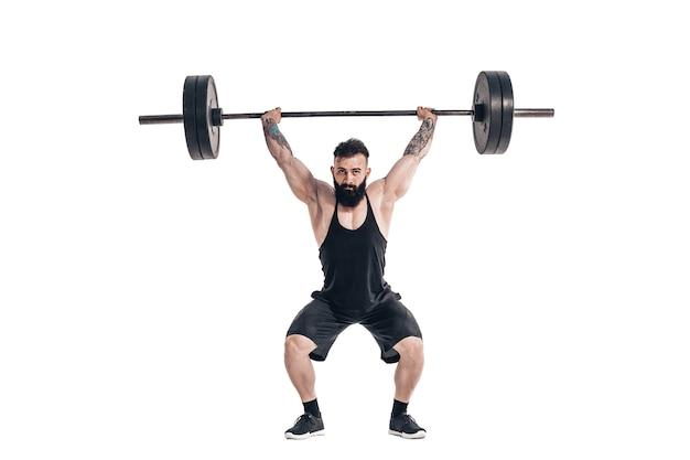La técnica de hacer un ejercicio de peso muerto con una barra de un musculoso fuerte tatuado barbudo deportes