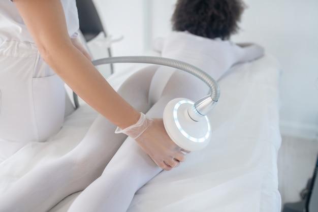 Técnica de hardware. chica delgada en ropa blanca especial acostada sobre su estómago y manos de esteticista con un aparato