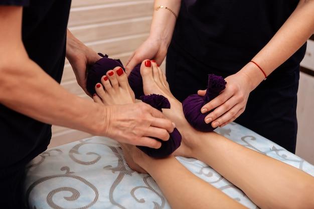 Técnica de masaje inusual. mujeres trabajadoras en uniforme negro masajeando los pies limpios de su cliente con bolsas apretadas llenas de hierbas
