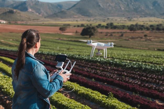 Técnicas jóvenes volando un avión no tripulado en un campo de lechugas