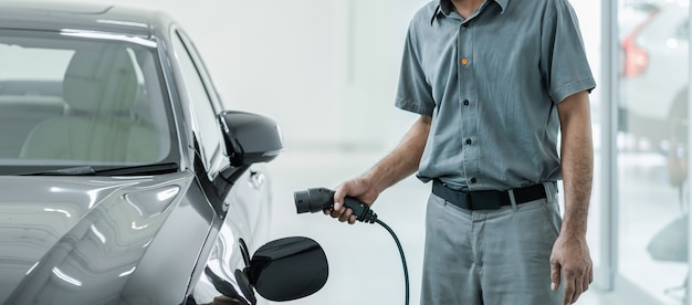 Técnico asiático senior está cargando el automóvil eléctrico o ev en el centro de servicio para su mantenimiento, concepto de energía alternativa ecológica