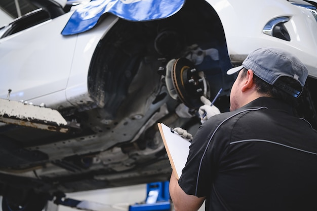 Técnico de automóviles asiático, mantenimiento de automóviles para clientes según el vehículo especificado