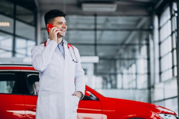 Técnico de automóviles con estetoscopio en una sala de exposición de automóviles hablando por teléfono