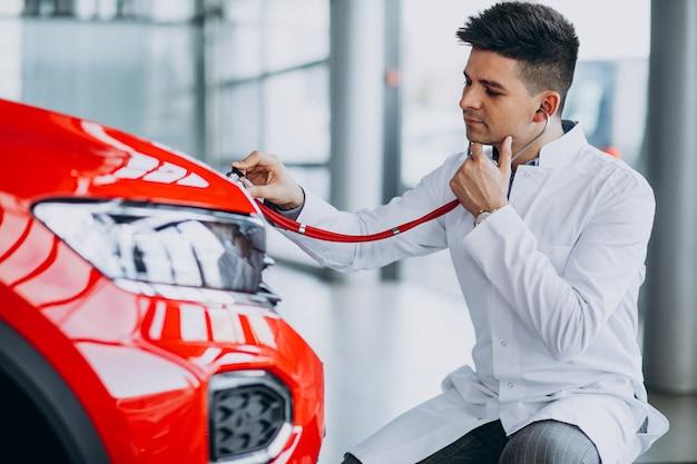 Técnico de automóviles con estetoscopio en una sala de exposición de automóviles