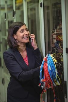 Técnico con cable de conexión mientras habla por teléfono móvil