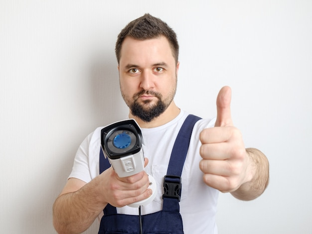 Técnico con cámara de seguridad cctv mostrando pulgares arriba gesto