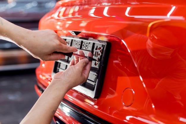 Técnico cambiando el número de placa del coche en el centro de servicio.
