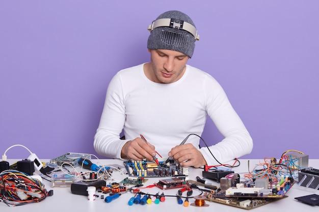 Técnico concentrado que repara el interior del teléfono inteligente o la computadora portátil con un multímetro en el laboratorio