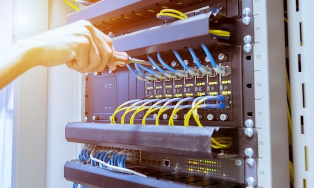 Técnico de conexión de cable de red al conmutador.