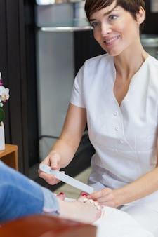 Técnico de uñas que presenta uñas de dedos de mujer