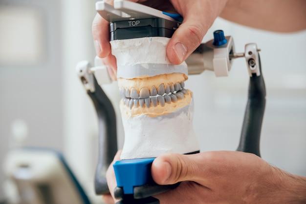 Técnico dental trabajando con articulador en laboratorio dental