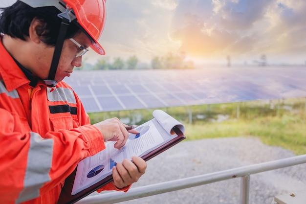 El técnico eléctrico e instrumentista hace una nota en el cuadro eléctrico del sistema eléctrico en el campo del panel solar