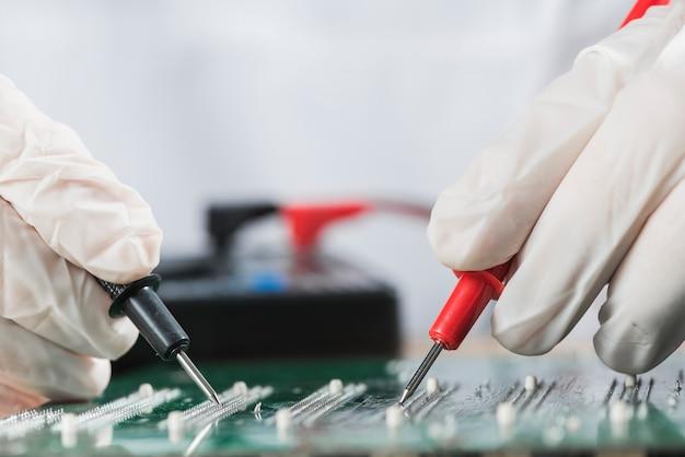 Técnico examinador de la placa de circuito de computadora con multímetro digital