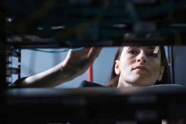 Técnico femenino hermoso serio que mira el servidor de datos y lo verifica mientras hace su trabajo