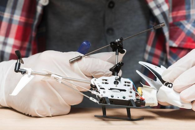 Técnico con guantes reparando helicóptero de juguete.