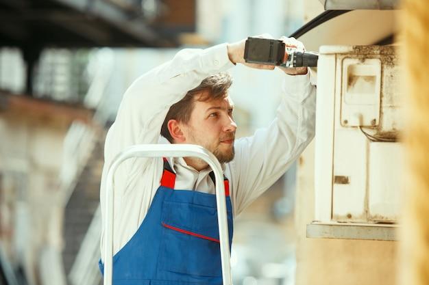 Técnico de hvac trabajando en una parte del condensador para la unidad de condensación
