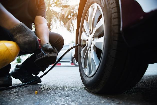 El técnico está inflando el neumático del automóvil - concepto de seguridad del transporte del servicio de mantenimiento del automóvil