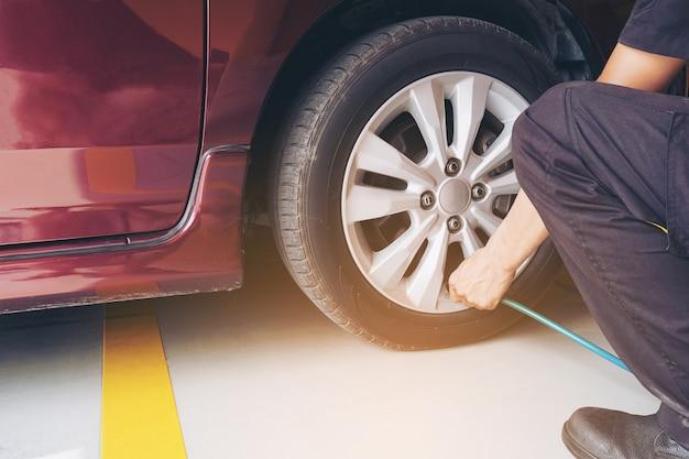El técnico está inflando el neumático del automóvil - concepto de seguridad de transporte del servicio de mantenimiento del automóvil