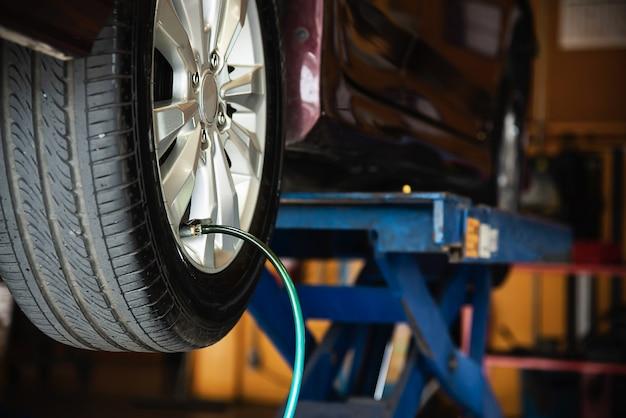 El técnico está inflando el neumático del automóvil, servicio de mantenimiento del automóvil, seguridad de transporte