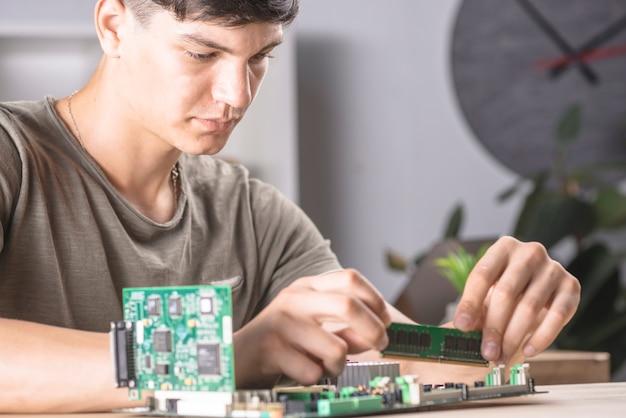Técnico informático masculino que inserta la memoria ram en la placa base de la computadora