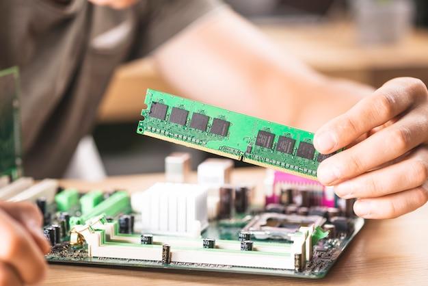 Técnico informático masculino que instala la memoria ram en la placa base