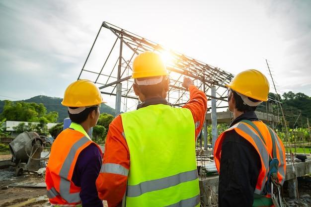 Técnico ingeniero observando el equipo de control de trabajadores en trabajadores de la construcción con ropa de seguridad y discutiendo en el sitio de construcción revisando el portátil de la oficina en el sitio de construcción