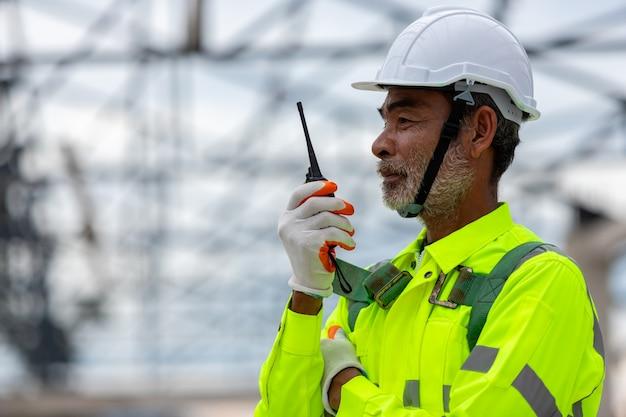Técnico ingeniero senior asiático observando el control de la construcción en la construcción de estructuras de techo en construcción