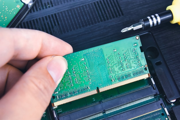 Un técnico instala una ram en una computadora portátil (memoria de acceso aleatorio)