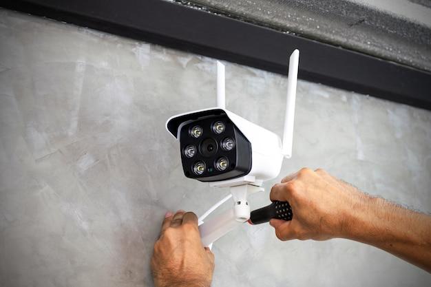 Técnico instalando cámara cctv inalámbrica en la pared