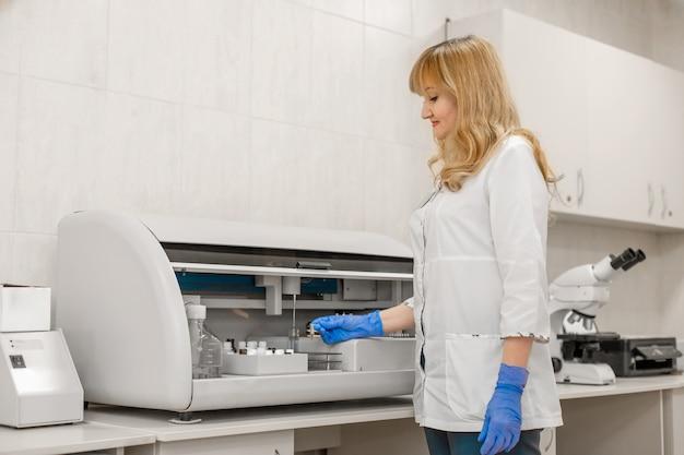 El técnico de laboratorio analiza la sangre en un analizador automático de muestras de sangre.