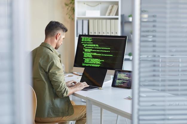 Técnico maduro sentado en su lugar de trabajo frente al monitor de la computadora y escribiendo en la computadora portátil en la oficina de ti