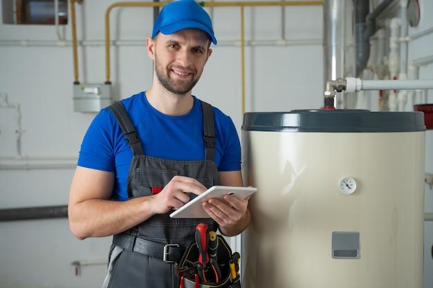 Técnico de mantenimiento de un calentador de agua caliente hombre comprobar el equipo del termómetro de la sala de calderas