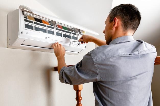 Técnico masculino limpieza de aire acondicionado en interiores