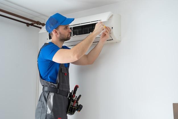 Técnico masculino en monos y una gorra azul repara un acondicionador de aire en la pared