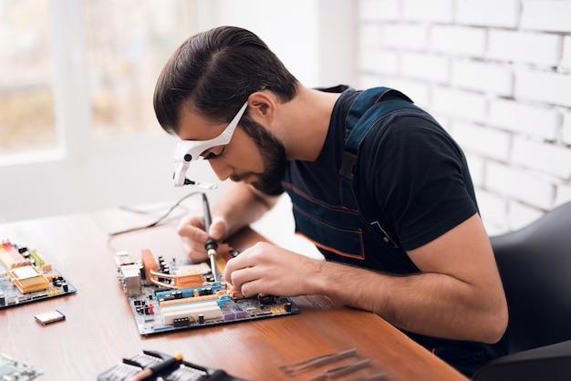 Técnico de master man soldering computer board.
