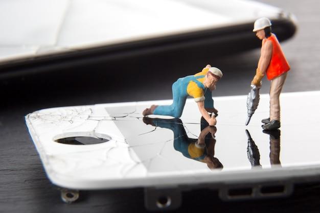 Técnico en miniatura personas reparando una pantalla rota del teléfono inteligente