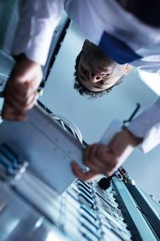 Técnico profesional de sexo masculino que saca el servidor blade y tiene la intención de comprobarlo mientras trabaja con el servidor de datos.