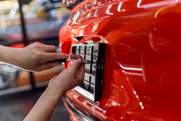 Técnico que cambia el número de placa del coche en el centro de servicio.