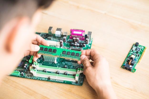 Técnico que prueba la ram de la placa base de la computadora en la mesa
