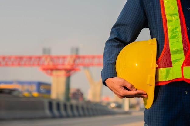 Técnico que sostiene el fondo de la luz del sol del casco de seguridad del sombrero amarillo