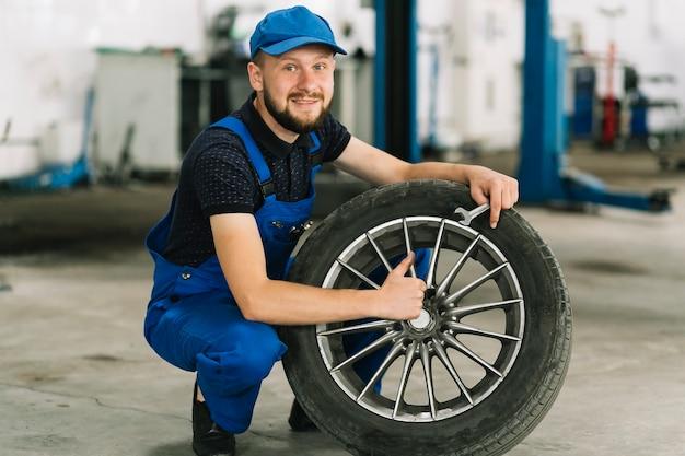 Técnico que sostiene la rueda en el garaje