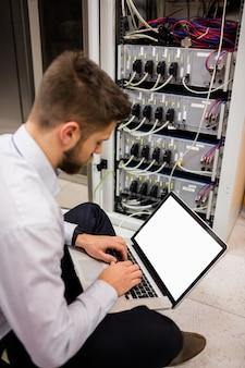 Técnico que usa una computadora portátil mientras analiza el servidor