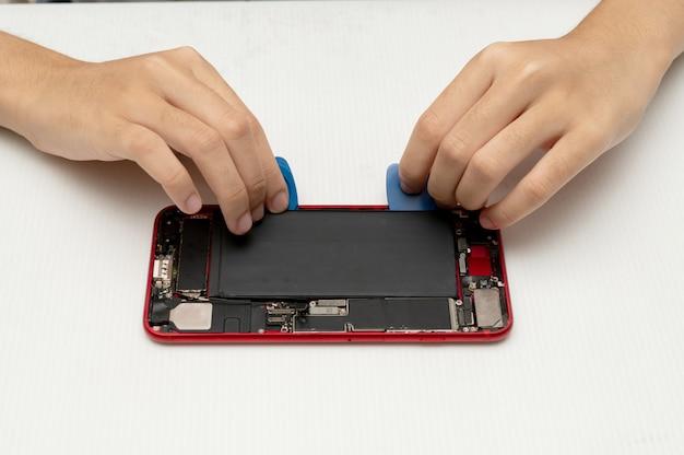 El técnico reemplaza la batería de un teléfono celular o teléfono inteligente.