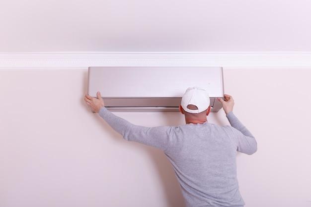 Técnico de reparación de aire acondicionado en la pared. filtro sucio de aire acondicionado en manos femeninas. mantenimiento de limpieza y lavado.