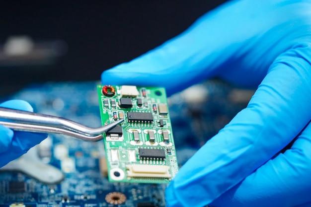 Técnico de reparación en el interior del disco duro con soldador.