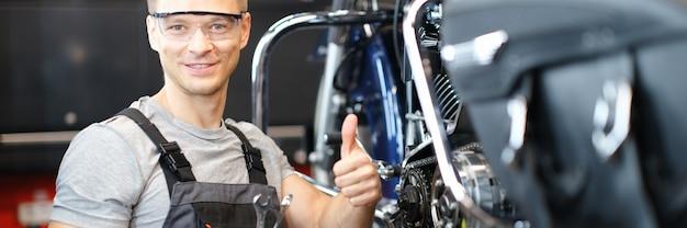 Técnico de reparación de motocicletas sostiene los pulgares hacia arriba mientras está de pie en el taller