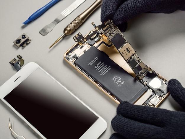 Técnico de reparación de teléfono inteligente roto en el escritorio